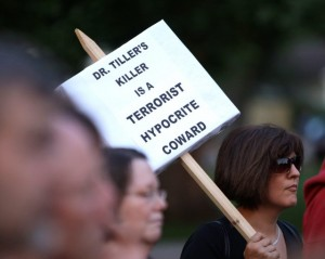Janet FitzGerald holds a sign during a May 31 candlelight vigil for Dr. George Tiller at a park in Lawrence, Kan. (Associated Press)