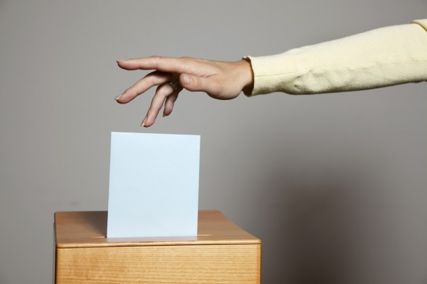 Young woman in a voting booth via Shutterstock