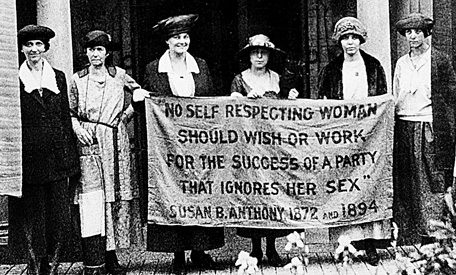 National Woman's Party members standing in front of their headquarters three months ago, with a banner that seems as relevant now as it did during the suffrage struggle. (Image marked for reuse in Google Images.)