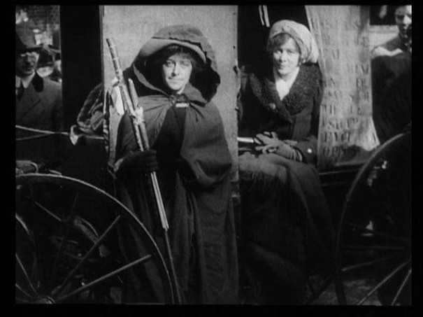 """General"" Rosalie Jones standing outside Elizabeth Freeman's literature (""ammunition"") wagon, as Freeman sits inside."
