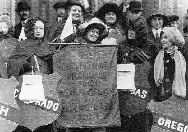 Rosalie Jones holding up the the hike's official banner (made before road conditions forced a start in Newark, rather than New York City, where the kickoff rally was held), with Ida Craft to the left holding up a shield with the name of the suffrage State of Colorado and Elizabeth Freeman on the far right, holding up the name of Oregon, another State where women have equal suffrage.