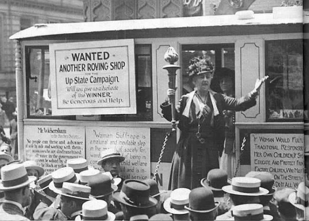 Louisine Havemeyer speaking to a crowd from a small, roving version of the Suffrage Shop.