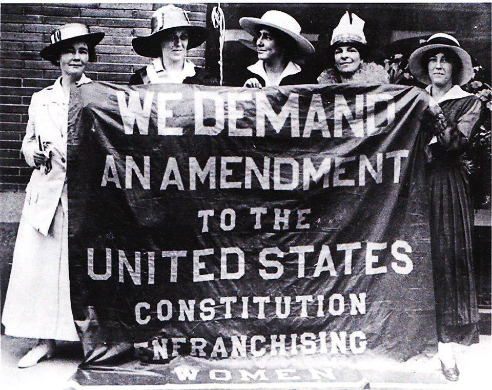 "Ann Martin (far left) and Sara Bard Field (far right) pose behind the ""Great Demand"" banner of the Congressional Union for Woman Suffrage."