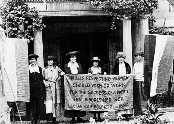 "Members of the National Woman's Party standing outside their national headquarters in Washington, D.C., displaying one of the banners they were about to pack up and take with them to next week's 1920 Republican National Convention. Alice Paul is standing above the word ""woman"" in the banner, which reads: "" 'No self respecting woman should wish or work for the success of a party that ignores her sex.' Susan B. Anthony 1872 and 1894."""