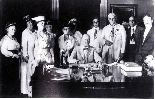 Speaker of the House Frederick H. Gillett signing the suffrage resolution, surrounded by members of the National American Woman Suffrage Association and leading pro-suffrage members of the House.