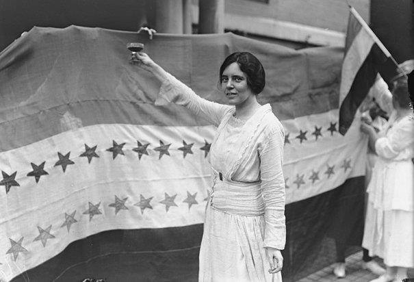 Alice Paul drinking a grape-juice toast to victory yesterday in front of her 36-star ratification flag.