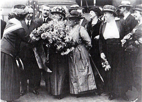 Carrie Chapman Catt holding the bouquet presented to her as she arrived in New York earlier today.