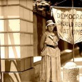"Betty Gram, of Portland, Oregon, picketing along the White House fence carrying a banner reminding President Wilson that ""DEMOCRACY SHOULD BEGIN AT HOME."""