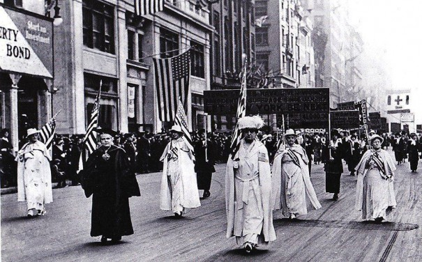 Carrie Chapman Catt, up front and near the center, and Rev. Anna Howard Shaw, in cap and gown on the left, lead at least 20,000 marchers in a suffrage parade down Fifth Avenue a week ago.