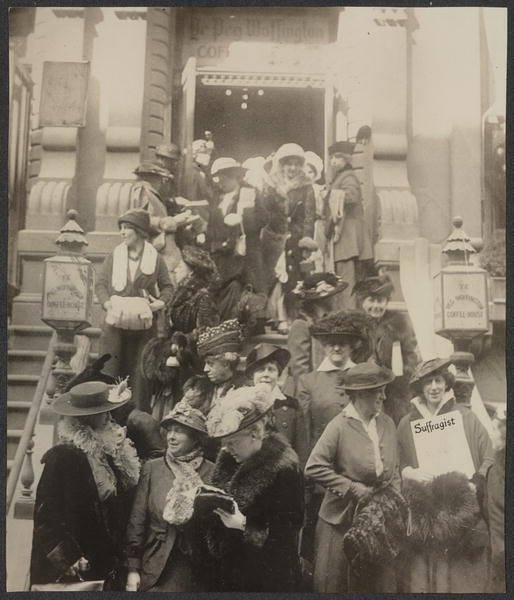 """Members of the Congressional Union leaving Peg Woffington's Coffee House in New York City, where the early session of their meeting today was held. The """"Suffragist,"""" seen in the lower right corner, is the C.U.'s official publication. Front row, from left: Elizabeth Colt, Elizabeth Kent, Elizabeth Selden Rogers, Olive Halladay Hasbrouck, with Hazel MacKaye holding the magazine. Second row: Marie Theodosia Armes, Lucy Burns and Jessie Davisson."""