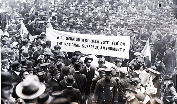 Suffragists surrounded by a crowd of onlookers as they prepared to march to Senator O'Gorman's office to quiz him about his views on suffrage.